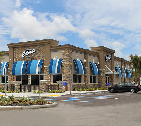 A Culver's restaurant on a bright day with white clouds above the restaurant